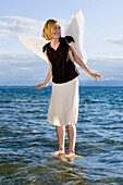 Mid adult woman wearing angel wings standing in lake Starnberg, Bavaria, Germany