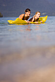 Two young women, girls, swimming in the lake on an air mattress, Lake Walchensee, Upper Bavaria, Bavaria, Germany