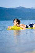 Young woman on airbed on lake Walchensee, Bavaria, Germany