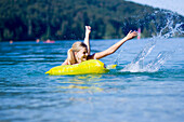 Young woman on an airbed on lake Walchensee splashing with water, Bavaria, Germany