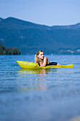 Young woman on an airbed on lake Walchensee, Bavaria, Germany