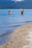 Two young women playing with a ball in lake Walchensee, Bavaria, Germany