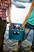 Two young women carrying a case of beer, Munich, Bavaria, Germany