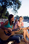 Two young women sitting at river Isar in the evening, Munich, Bavaria, Germany