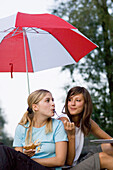 Two young women sitting under an umbrella while eating, Munich, Bavaria, Germany