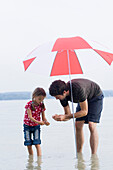 Father and daughter (3-4 years) searching for mussels in lake Ammersee, Bavaria, Germany