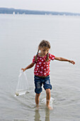 Girl (4-5 years) looking for shells in the lake, Lake Ammersee, Bavaria, Germany