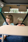 Two girls (2-4 years) sitting in a motorhome