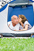 Senior couple lying in their tent, Woman kissing man, Holiday, Bavaria, Germany