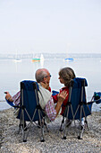 Senior couple sitting in folding chairs at lake Ammersee, Bavaria, Germany