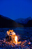 Young couple sitting in front of a camp fire, kissing, Lenggries, Upper Bavaria, Bavaria, Germany
