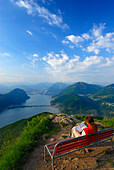 Mid adult woman sitting on a bench, Lake Lugano in background, Monte San Giorgio, Ticino, Switzerland