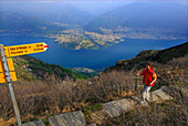 Mid adult woman ascending Monte Gambarogno from Alpe di Neggia, view to lake Lago Maggiore, Ticino, Switzerland