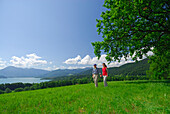 young couple hand in hand on pasture with view to lake Tegernsee, Bavarian foothills, Bavarian range, Upper Bavaria, Bavaria, Germany
