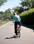 Man on bicycle in the summer heat, near boat harbour in Burg-Kauper, Upper Spreewald, biosphere reservat, Spreewald, Brandenburg, Germany