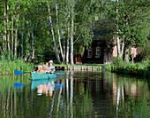 Familiy kayaking in front of an old traditional style farm house, birch trees, Lehder Graben, village of Lehde, Upper Spreewald, biosphere reservat, Spreewald, Brandenburg, Germany