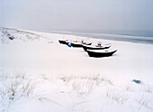 Snow covered boats at beach, Baabe, Rugen island, Mecklenburg-Western Pomerania, Germany