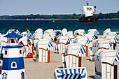 People and beach chairs on the beach, ship in the background, Travemünde, Schleswig Holstein, Germany, Europe