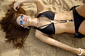 Attractive upscale woman, lying on beach.  She is wearing sunglasses, necklace, and bracelet with her black bikini, and is holding her hair.
