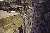 Two people lie precariously on the edge of great slab overlooking the Cliffs of Moher near Lahinch. Co. Clare, Ireland