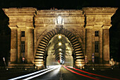The monumental entrance to the road tunnel that runs through Castle Hill on Clark Adam Ter by night, Budapest, Hungary.