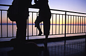 Sunrise seen from a ship going from Barcelona to Menorca with two people silhouettes in the deck, leaning on the handrail. Arriving to the island. Spain.