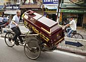 Man transporting a coffin on rickshaw. Hanoi. Vietnam.