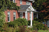 New England cottage surrounded by bushes, flowers and autumn fall trees