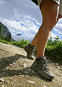 Female hikers legs on Highline Trail with Reynolds Peak in background, Glacier National Park, Montana, USA