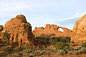 Skyline Arch and towering sandstone buttes catch the last rays of warm light on a chilly winter afternoon, Arches National Park, Utah, USA.