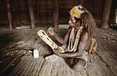 Asmat man carving a statue, Western Papuasia, Former Irian-Jaya, Indonesia
