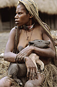 Dani woman holding a piglet in her arms, Baliem valley, Western Papuasia, Former Irian-Jaya, Indonesia