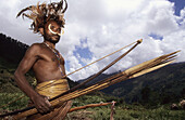 Yalis hunter with nose adornment made of wild pigs bones, rooster feathers head-dress, long penis case, bow and arrows, Western Papuasia, Former Irian-Jaya, Indonesia