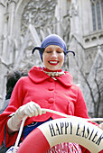 Easter Parade. Easter Sunday (April). New York City. Manhattan. 5th Ave. Woman standing next to St. Patricks Catedral holding a life saver that reads Happy Easter.