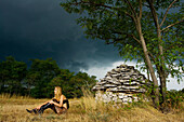 Young woman in front of Istrian kazun stone hut just before the storm, Croatia, Europe