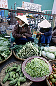 An outdoor green grocer sells cabbages, tomatoes and bittermelon (Hu Qua). Kon Tum. Kon Tum province. Vietnam.