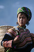 An ethnic flowery Hmong girl on Northern Vietnam wears highly colourful clothing. Can Cau. Lao Cai province. Vietnam.