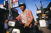 A Balinese man on a motorbike in downtown Kuta Beach. Bali.