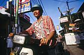 A Balinese man on a motorbike in downtown Kuta Beach. Bali.