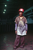 A factory worker in Beijing takes a break from work. His clothes are dirty from the work, manufacturing car parts, outside Beijing. China.