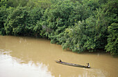 Wooden canoe with two people in it sailing on a brown river. Ivory Coast