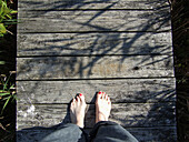 Bare feet on a dock in Mattituck, NY. Mattituck is on the South Shore of the North Fork of Long Island. The feet are of a woman, with half worn polish, and bunions, on a sunny day with her jeans rolled up. USA.