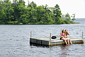 sisters 13 and 18 yrs sitting on dock together at cottage