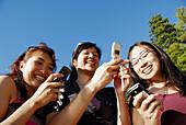 3 asian women each using cell phones