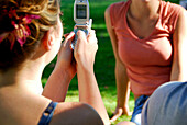 female getting ready to take photo of another female with cellphone