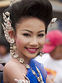 Young Thai woman smiles at Candle Festival parade, Ubon Ratchatani, Thailand
