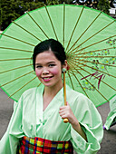 smiling under a parasol. Woman in a kimono at the Sinulog Festival, Philippines