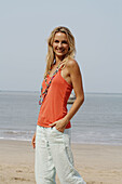 Portrait of a beautiful blonde woman wearing an orange vest and smiling on a beach in India.