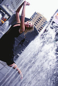 An aspiring actress gleefully runs through a series of fountains situated right in the midst of downtown Toronto Canada.  Shot in October, 2006