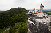Three young people, a woman and two men rock climbing on sandstone rocks, Papststein, Elbe Sandstone Mountains, Saxon Switzerland, Saxony, Germany